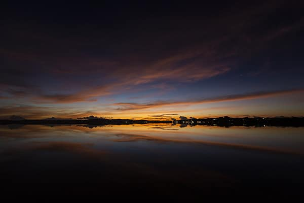 Sunrise time-lapse with red sky reflected on calm water