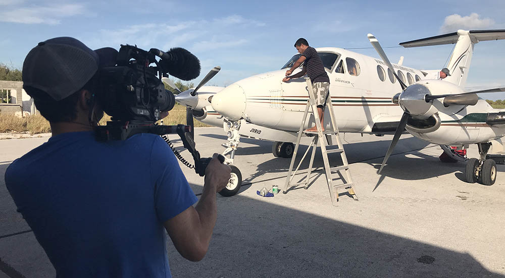 Documentary cameraman Electronic News Gathering (ENG) filming small aircraft
